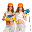 Gemini girls in orange helmets with an electric drill and electric saw on a white background. — Foto de Stock