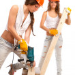 Stock Photo: Gemini girls in orange helmets with an electric drill and electric saw on a white background.