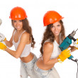 Gemini girls in orange helmets with an electric drill and electric saw on a white background. — Стоковая фотография