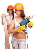 Garotas gemini em capacetes laranja com uma furadeira elétrica e elétrica viram sobre um fundo branco. — Foto Stock