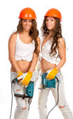 Gemini girls in orange helmets with an electric drill and electric saw on a white background. — Fotografia Stock