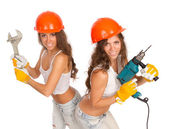 Gemini girls in orange helmets with an electric drill and electric saw on a white background. — Stock Photo