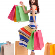A girl in a long dress color, standing with shopping bags on white background. — Stock Photo #16777699