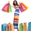 A girl in a long dress color, standing with shopping bags on white background. — Stock Photo #16777711