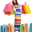 A girl in a long dress color, standing with shopping bags on white background. — Stock Photo #16777713
