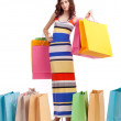 A girl in a long dress color, standing with shopping bags on white background. — Stock Photo #16777719