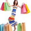 A girl in a long dress color, standing with shopping bags on white background. — Stock Photo #16777721