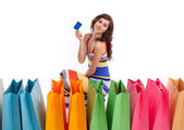 Woman in colored long dress, standing next to a shopping bag with a credit card on a white background. — Stock Photo