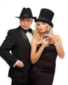 Mann und frau in eleganten anzügen und hüte mit einem revolver — Stockfoto