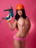 Brunette in pink panties with suspenders in the construction helmet with an electric drill on a pink background — Stock Photo