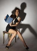Kız bir sandalyede oturuyor ve korkunç bir kitap okuma — Stok fotoğraf