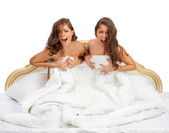 Twin sisters startled cry sitting in bed — Stock Photo