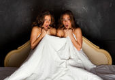Twin sisters sitting on the bed and screaming in terror — Stock Photo