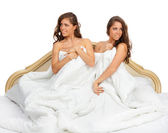 Twin sisters sitting on the bed — Stock Photo