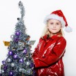 Foto Stock: Little girl preparing christmas tree
