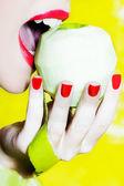 Kvinna porträtt bitting ett äpple — Stockfoto