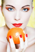 Woman portrait holding a mandarine — Stock Photo