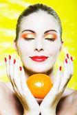 Woman Portrait smelling a citrus fruit smiling — Stock Photo
