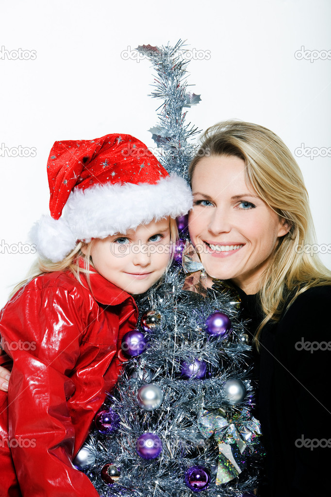 Indoors picture of a little girl with her mother preparing christmas tree on isolated white background  Stock Photo #13653774