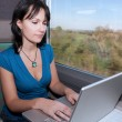 Woman in a train computing laptop computer - Stock Photo
