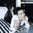 Stock Photo: Womin bedroom computing pensive