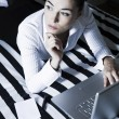 Woman in a bedroom computing thoughtful — Stock Photo #13668165