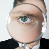 Curious woman looking eyes through magnifying glass — Stock Photo