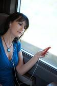 美丽的年轻女子在听音乐的 mp3 播放器 ipod 类型一列火车在做梦 — 图库照片