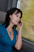 Beautiful young woman in a train smiling and making a phone call — Stock Photo