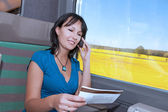 Beautiful young woman in a train making a phone call with a ticket in his hand — Stock Photo