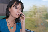 Beautiful young worried woman in a train making a phone call — Stock Photo