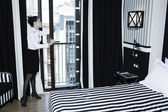 Woman chambermaid cleaning in a hotel bedroom — Stock Photo