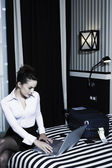 Woman computing in a hotel bedroom — Stock Photo