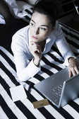 Woman in a bedroom computing thoughtful — Stock Photo