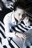 Woman in a bedroom internet surfing — Stock Photo