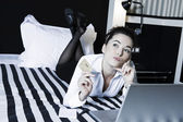 Woman in a bedroom hold credit card pensive — Stock Photo