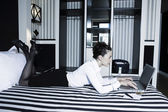 Woman in a hotel bedroom computer internet surfing — Stock Photo