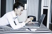 Woman in a hotel bedroom shopping on internet — Stock Photo