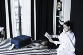 Woman reading a book in a hotel bedroom — Stock Photo