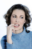 Studio shot portraits of a young annoyed woman biting his finger — Stock Photo