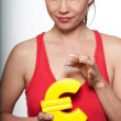 Portrait of beautiful woman with small savings and Euro shaped p — Stock Photo
