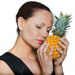 Closeup portrait of beautiful woman smelling pineapple with eyes — Stock Photo