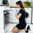 Beautiful caucasian woman in a kitchen waiting with anxiety in front of the oven — Stock Photo