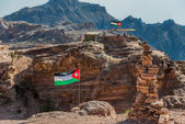 Jordan flags floating in nabatean city of petra — Stock Photo