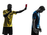 Two men soccer player and referee showing red card silhouette — Stock Photo