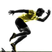 Corredor de joven velocista en los podiums silueta — Foto de Stock