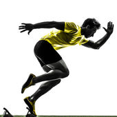 Mladý muž sprinter běžec v startovací bloky silueta — Stock fotografie