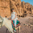 Stock Photo: Tourist riding donkey in nabatecity of petrjordan