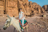 Tourist riding donkey in nabatean city of petra jordan — Stock Photo