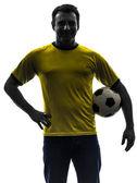 Hombre que sostiene la silueta de fútbol soccer — Foto de Stock